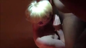 Mature Russian blonde with blonde hair is sucking a very big, black cock, while kneeling on the floor